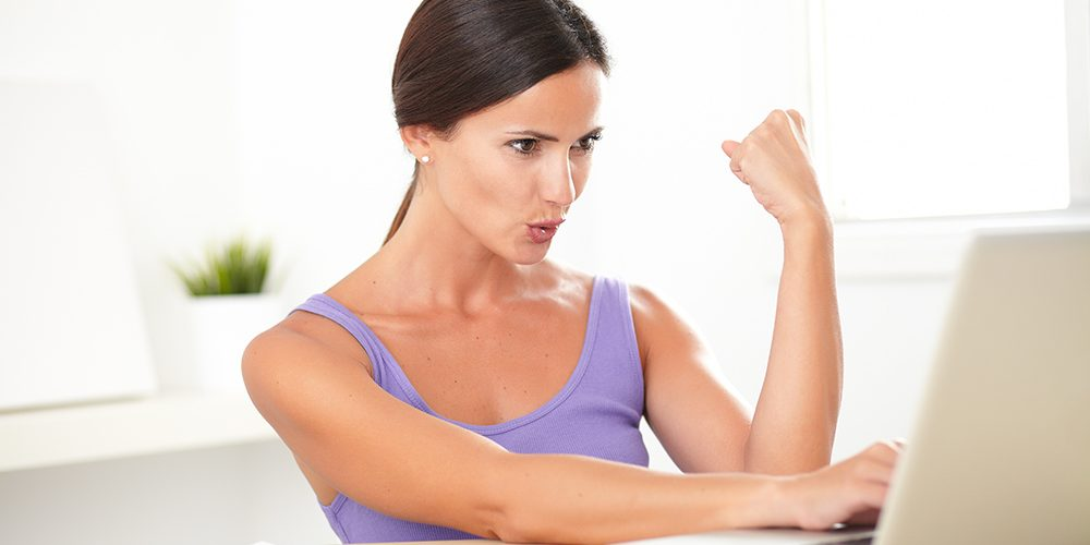 Excited young woman in purple shirt sitting and working on laptop as freelancer at home